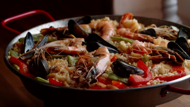 preparing seafood paella with shrimps, squid, mussels, green beans and paprika - spanish culture stock videos & royalty-free footage
