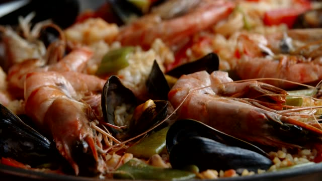 preparing seafood paella with shrimps, squid, mussels, green beans and paprika - mediterranean food stock videos & royalty-free footage