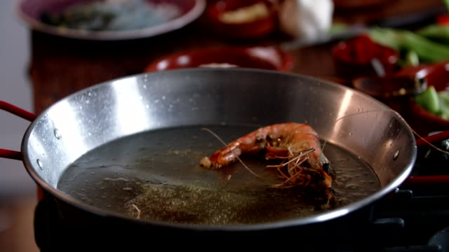 preparing seafood paella with shrimps, squid, mussels, green beans and paprika - green bean stock videos and b-roll footage