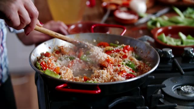 preparing seafood paella with shrimps, squid, mussels, green beans and paprika - cucina mediterranea video stock e b–roll