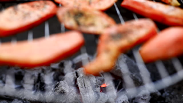 preparing sweet potato on a open flame grill. - kohle stock-videos und b-roll-filmmaterial