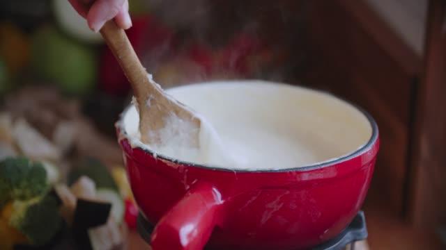 vidéos et rushes de préparer la fondue au fromage suisse dans une casserole, servie avec pain - fondre