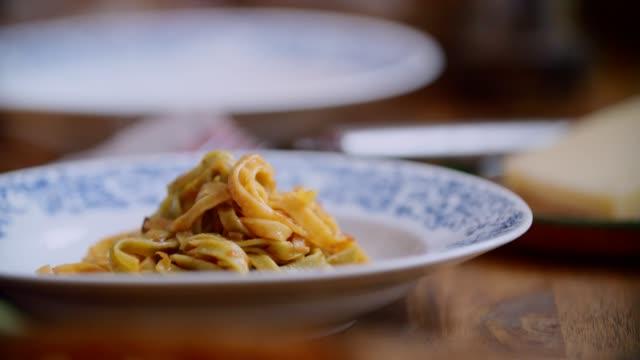 preparing tagliatelle pasta with vegan bolognese and bella lodi cheese - tagliatelle stock videos and b-roll footage