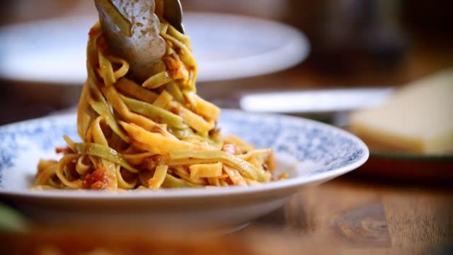 preparing tagliatelle pasta with vegan bolognese and bella lodi cheese - salsa di pomodoro video stock e b–roll