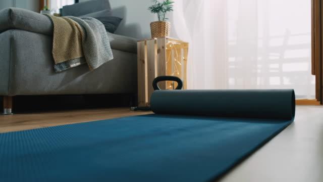 vídeos de stock, filmes e b-roll de slo mo preparando o ata de exercícios para se exercitar em casa - equipamento para exercícios