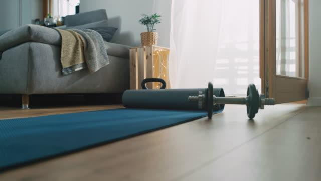 slo mo vorbereitung der trainingsmatte für das training zu hause - trainingsraum wohnraum stock-videos und b-roll-filmmaterial