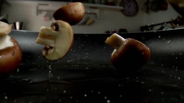 preparing vegan dish roasting mushrooms in a pan - mushroom stock videos & royalty-free footage