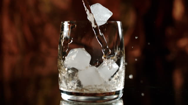slo mo preparing whisky on the rocks - scotch whiskey stock videos and b-roll footage