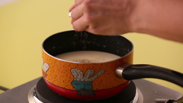 preparing white cream sauce adding milk to flour and butter in a pan and stirring, adding nutmeg salt and pepper to a white sauce - adding salt stock videos and b-roll footage