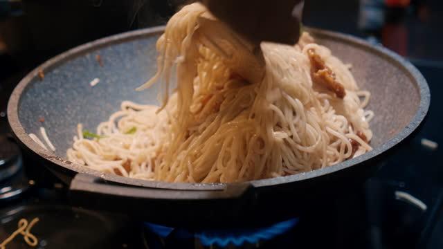 """ご自宅でアジア料理を食べなさい """"ヌードル"""" 醤油を混ぜる - 野菜と鶏を揚げる - テナガエビ点の映像素材/bロール"""