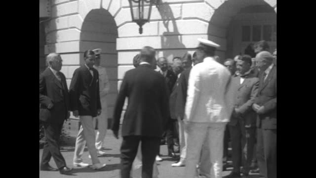 VS Pres Calvin and First Lady Grace Coolidge walk down exterior stairs of the White House wearing summer attire and join members of the Committee of...