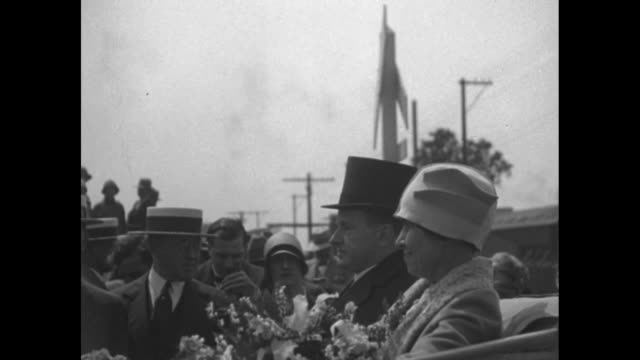 pres calvin coolidge and first lady grace coolidge getting off train / coolidge and grace getting into open car grace holding flowers / car carrying... - south dakota stock-videos und b-roll-filmmaterial