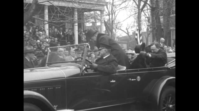 vidéos et rushes de pres calvin coolidge wearing an overcoat with fur lapels stands with gov harry byrd and both men doff their top hats / vs coolidge stands in the rear... - alexandria virginie