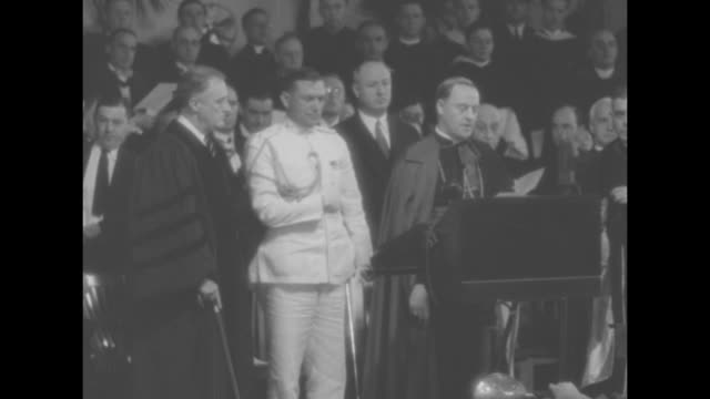Pres Franklin Roosevelt in cap and gown stands next to car with Patrick Cardinal Hayes Roosevelt's aide stealthily puts a cane behind himself Eleanor...