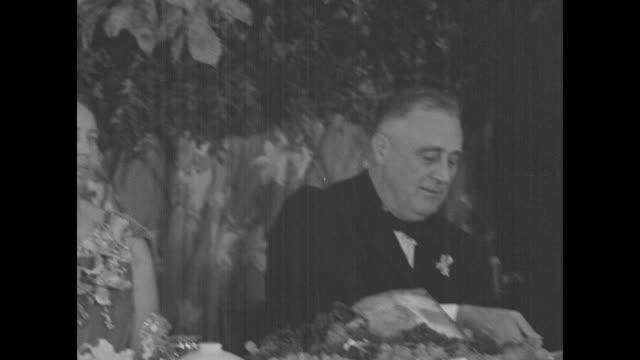 VS Pres Franklin Roosevelt seated at banquet table carves Thanksgiving turkey during holiday dinner at the Georgia Warm Springs Foundation as boy...