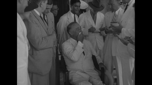 US Pres Franklin Roosevelt sitting in chair talking to reporters standing around him / CU US Marines officer James Roosevelt son of Franklin posing...