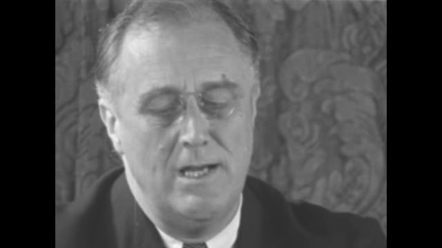 vídeos de stock e filmes b-roll de pres franklin roosevelt sitting in front of brocaded curtain and wearing pincenez reads excerpts of his fireside chat address to the nation during a... - franklin roosevelt