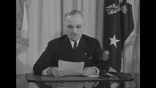 pres. harry s. truman sits at desk with two flags behind him; he reads speech into microphone; he is addressing the members of the us armed forces... - harry truman stock videos & royalty-free footage