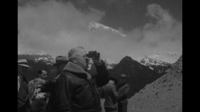 us pres harry truman in leather coat and stetson hat ties scarf assisted by aide maj gen harry h vaughan / vs truman looks through binoculars at mt... - mt rainier national park stock videos & royalty-free footage