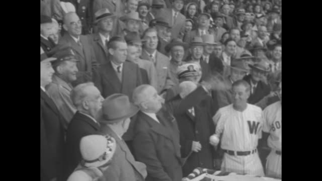 Pres Harry Truman in stands shaking hands with Red Sox manager Lou Boudreau Washington manager Stanley Harris hands him a baseball dignitaries...