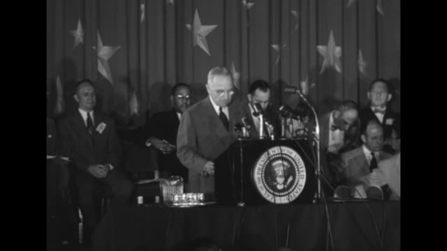 SOT Pres Harry Truman standing at podium in room in Statler Hotel giving speech denouncing tactic of political opponents officials sitting behind him