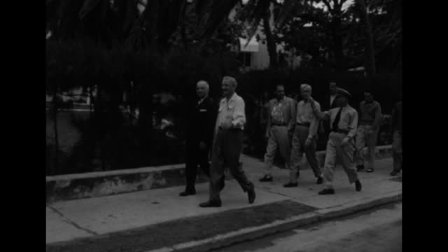 pres. harry truman, wearing suit and tie, walks along street with entourage in key west, fl, as he travels from the little white house to building... - ハリー トルーマン点の映像素材/bロール