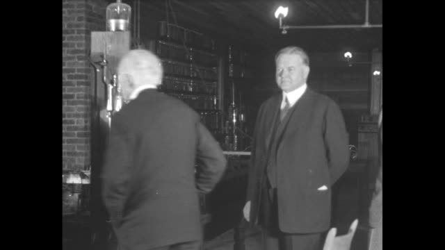 Pres Herbert Hoover with inventor Thomas Edison standing before probably his first electric light at the Light's Golden Jubilee celebration / CU...