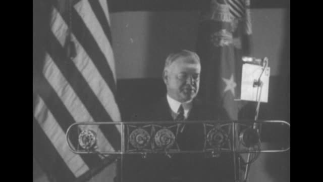 pres hoover standing at podium speaking into microphones us flag on one side of him american legion flag on other side during an address to the... - herbert hoover us president stock videos & royalty-free footage