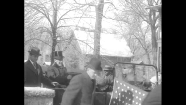 US Pres Woodrow Wilson coming down steps with officials and getting into open car he wears a top hat and all wear overcoats / men get into car with...