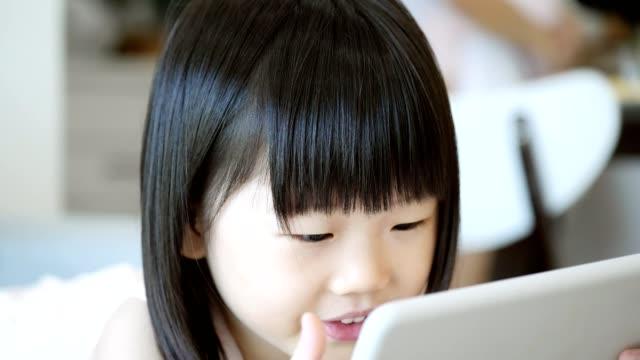 vorschulalter asiatin nutzt digitale tablet zu hause - wachsamkeit stock-videos und b-roll-filmmaterial