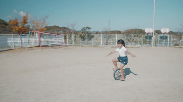 preschool age girl practicing on a unicycle as part of her preschool physical education - japanese school uniform stock videos & royalty-free footage
