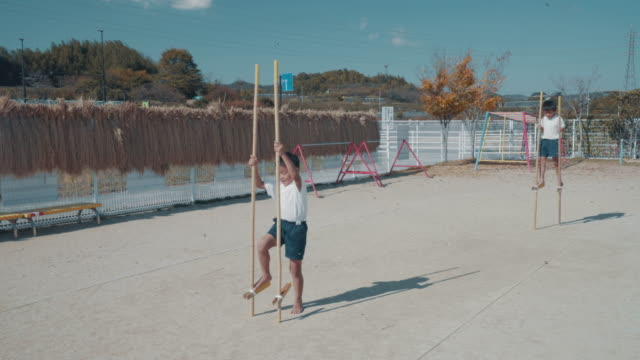 preschool aged boy learning to use bamboo stilts as part of his physical education - japanese school uniform stock videos & royalty-free footage