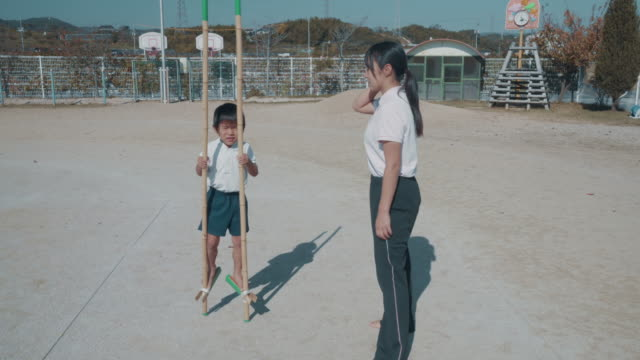 preschool aged boy learning to use bamboo stilts with support from his teacher as part of his physical education - japanese school uniform stock videos & royalty-free footage
