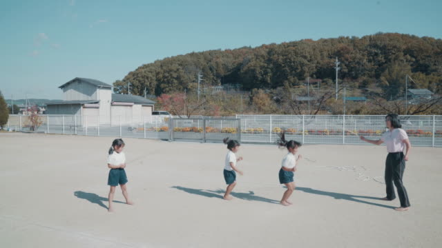 preschool aged children practicing with a jump rope with their teacher - 集中点の映像素材/bロール