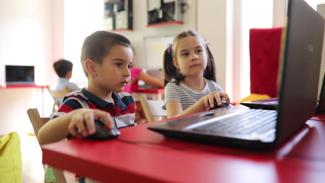 preschool boy and girl using laptops in private it school - preschool child stock videos & royalty-free footage