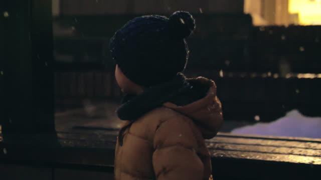 夜の雪の中で遊んでいる就学前の少年。 - 男の赤ちゃん一人点の映像素材/bロール