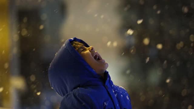 stockvideo's en b-roll-footage met kleuter die in de sneeuw bij nacht speelt. - muts