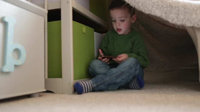 Preschool boy playing with smartphone in den