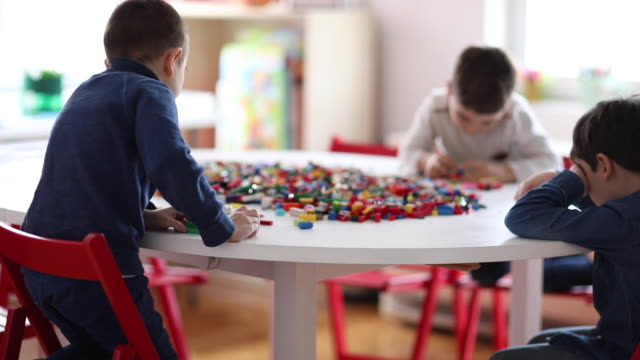 preschool boys playing with plastic blocks at playroom of private school - back lit stock videos & royalty-free footage