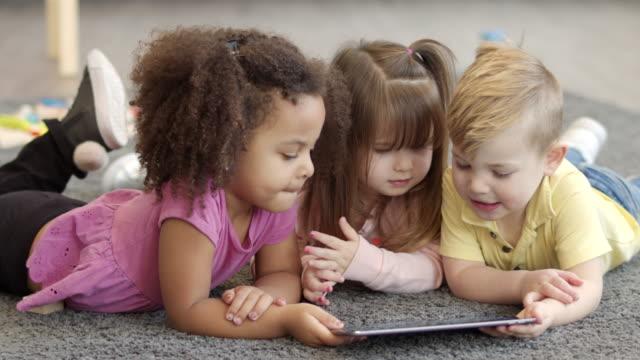 preschool friends reading a book - preschool child stock videos & royalty-free footage