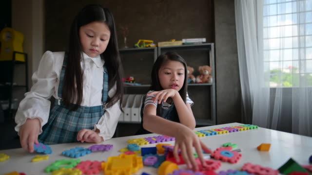 Kindergarten Mädchen Montage Puzzle Alphabet Puzzle am Tisch