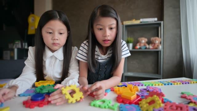 Vorschulmädchen, die Puzzle-Puzzle am Tisch zusammenstellen