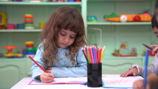 preschool girl drawing in book by friends at desk - colored pencil stock videos and b-roll footage