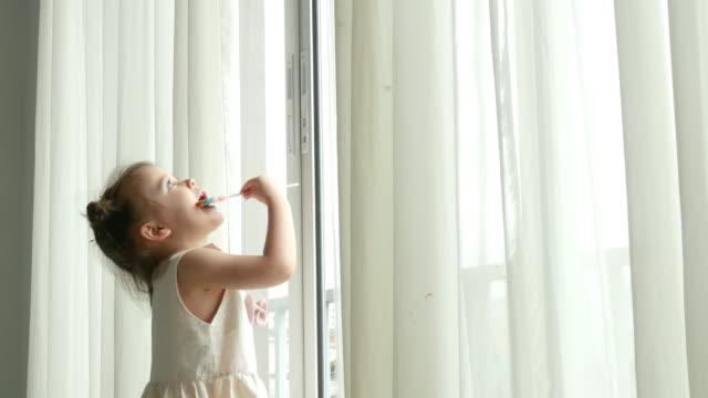 preschool girl eating lollipop , homeschooling concept - lollipop stock videos & royalty-free footage
