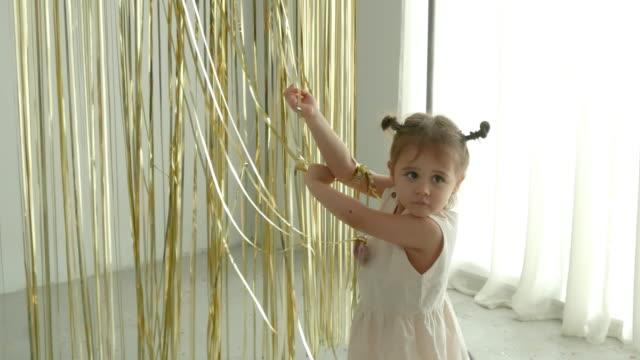 preschool girl playing peekaboo game with blind glitter ribbon - peekaboo game stock videos & royalty-free footage