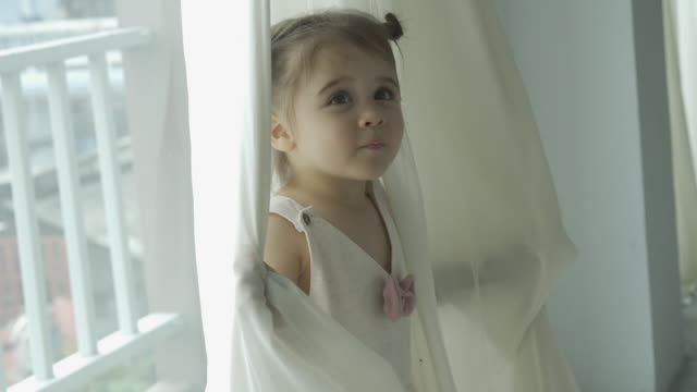 preschool girl playing peekaboo game with white transparent courtain - peekaboo game stock videos & royalty-free footage