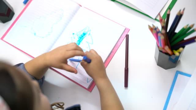 stockvideo's en b-roll-footage met preschool meisje gekrabbel in boek bij klas - peuterschool gebouw
