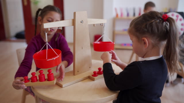 preschool girls playing in child care classroom - scales stock videos & royalty-free footage