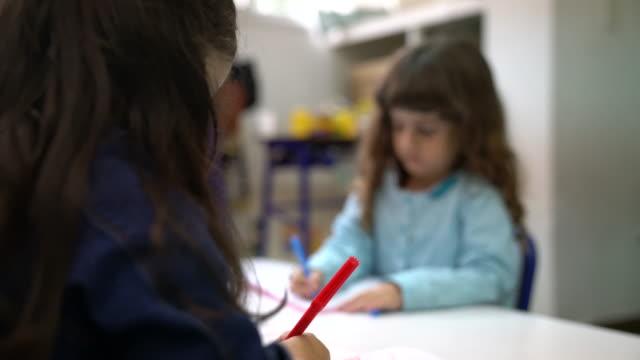 Preschool girls scribbling in books at desk