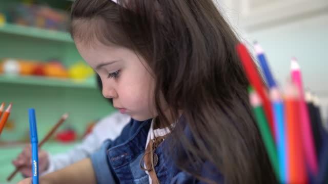 Preschool kids drawing in books at classroom